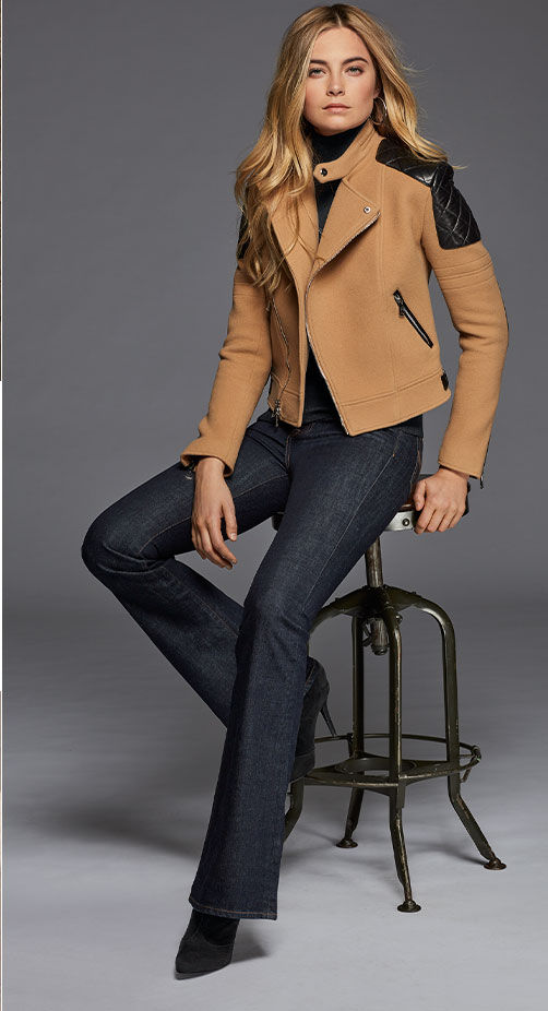 Woman models tan moto jacket with black shoulder patches & boot cut jean