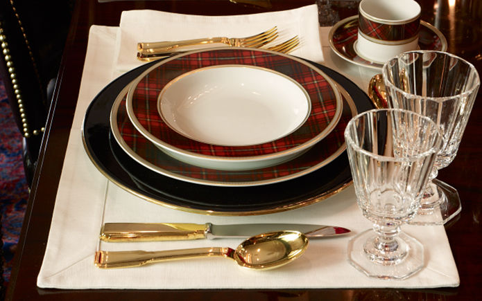 Place-setting with navy & plaid-patterned plates & gold flatware
