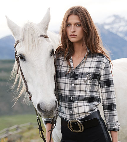 Woman stands next to white horse wearing black-and-white monogram shirt