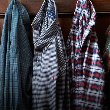 Button-down shirts in various patterns hang from row of hooks