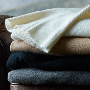 Stack of sweaters in grey, black, tan & cream