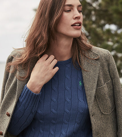Woman wearing blue cable-knit sweater under unbuttoned jacket
