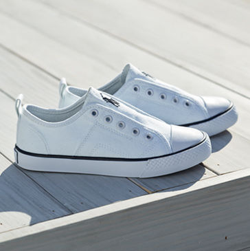 Pair of laceless white sneakers on wooden deck.